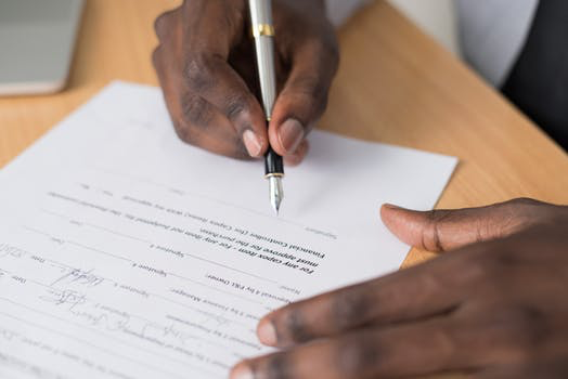 a black man signing a paper